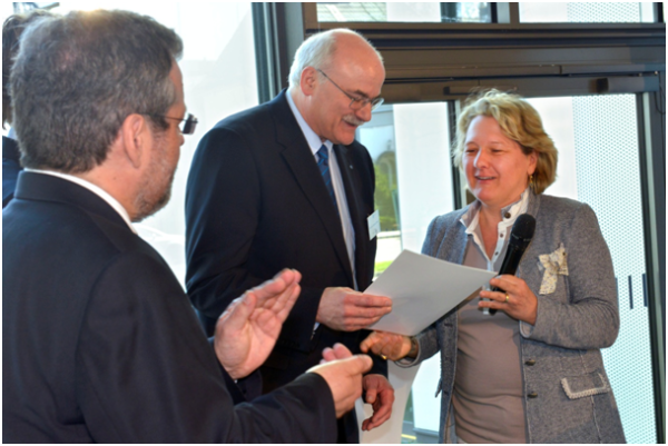 Mrs. Svenja Schulze, minister for innovation, science and research, surrenders the certificate of discharge with a lot of accolade to the President of the University of Applied Sciences Ruhr West. Left: Vicepresident Helmut Koestermenke
